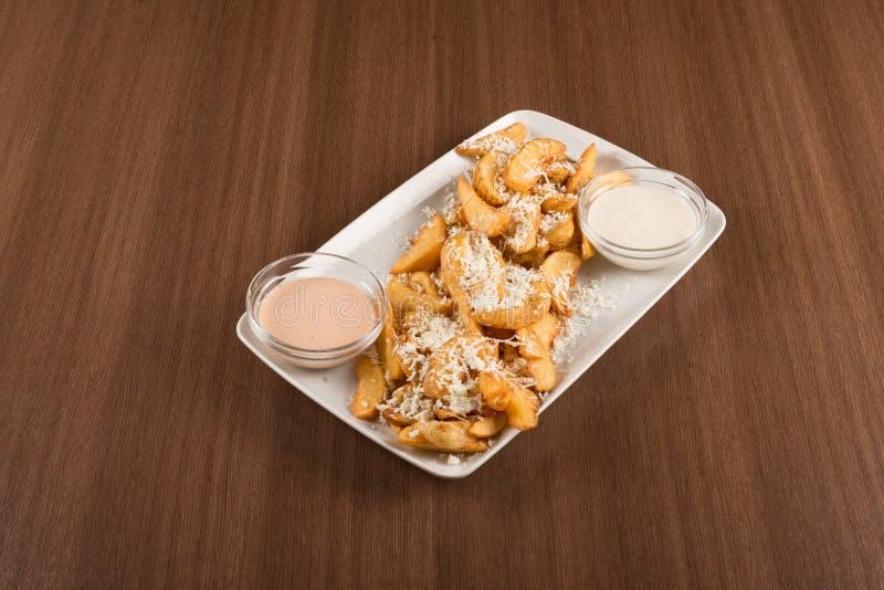 油煎的土豆用乳酪和调味汁 库存图片