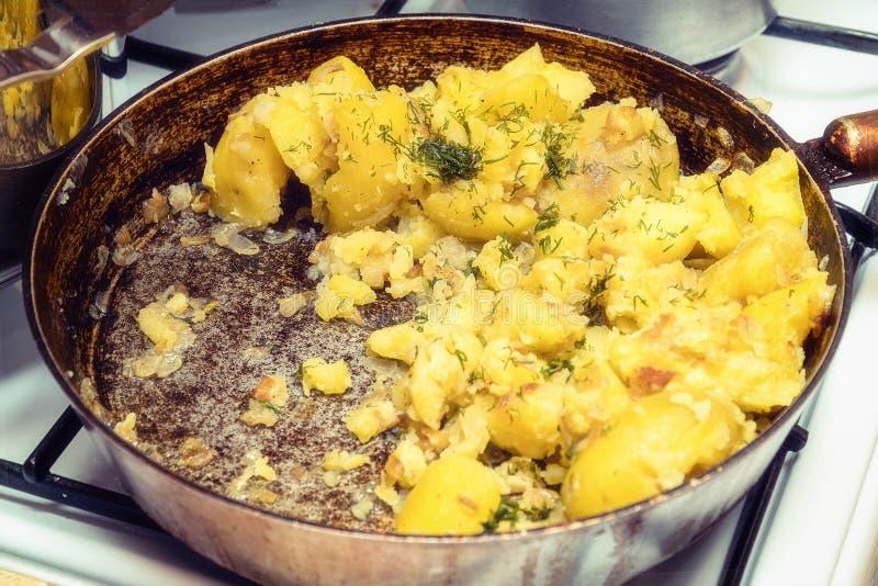 油煎的土豆用在一个平底锅的莳萝在煤气炉 库存图片
