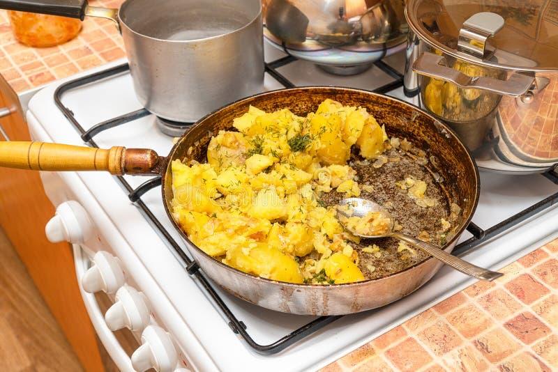 油煎的土豆用在一个平底锅的莳萝在煤气炉 免版税库存照片