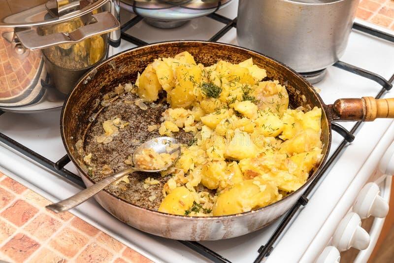 油煎的土豆用在一个平底锅的莳萝在煤气炉 免版税图库摄影