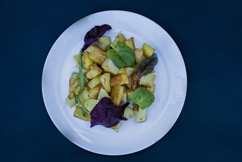 油煎的土豆用在一块白色板材的莴苣 ?? o 免版税库存照片