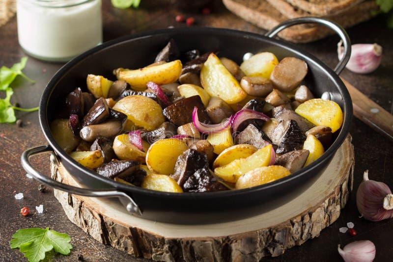 油煎的土豆用森林蘑菇、牛肝菌蕈类、葱和酸性稀奶油 在煎锅,在黑暗的素食秋天食物的土气盘 免版税图库摄影