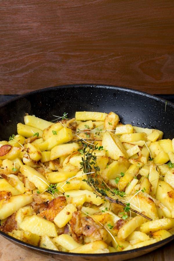 油煎的土豆用绿色新芽,在一个生铁煎锅的迷迭香在木背景 免版税库存照片