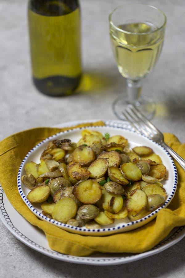 油煎的土豆用蘑菇和葱在白色板材有藤的在灰色背景假日晚餐的 免版税库存图片