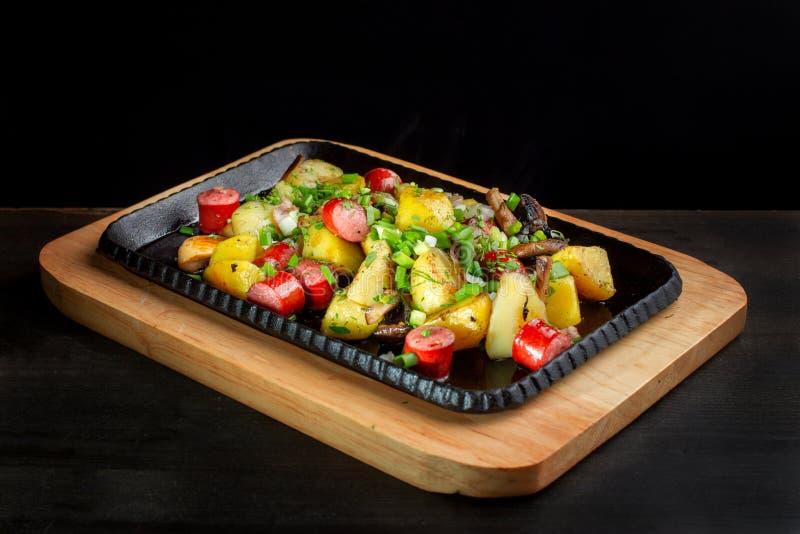 油煎的土豆用蘑菇和香肠在生铁煎锅 免版税库存照片