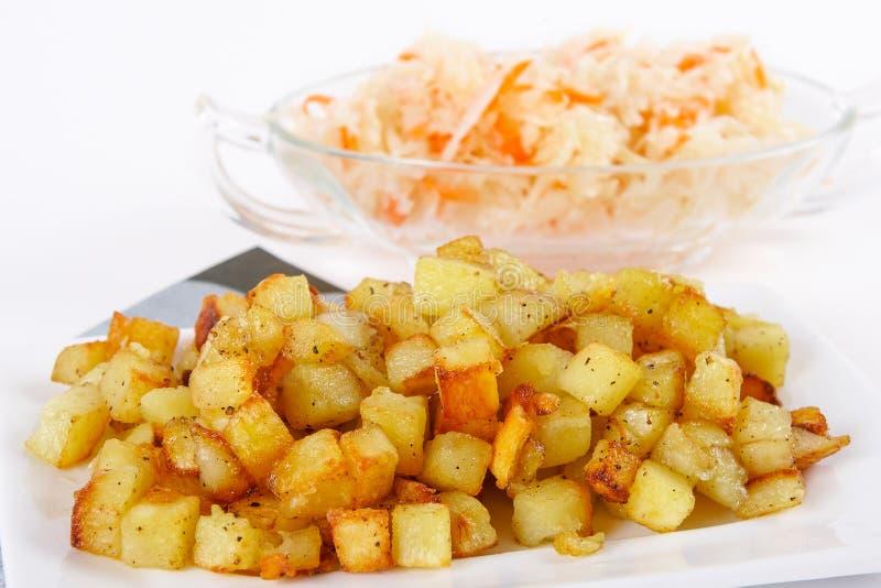 油煎的土豆立方体用酸圆白菜 免版税库存照片