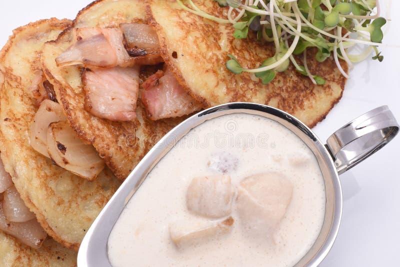 油煎的土豆薄烤饼用烟肉和蘑菇酱油 免版税图库摄影