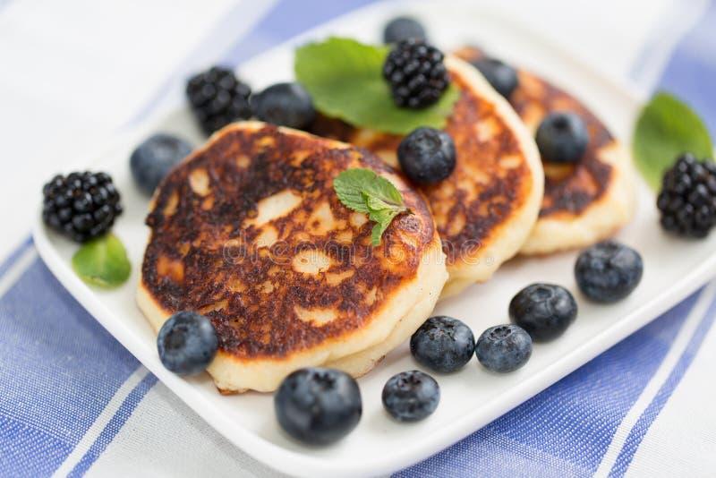 油煎的夸克乳酪结块用蓝莓 传统俄国甜syrniki 免版税库存图片