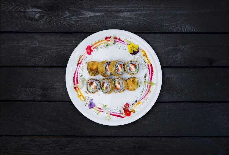 油煎的寿司用黄瓜、一些乳脂干酪、tobiko鱼子酱、三文鱼和鳗鱼 顶视图 黑色木背景 免版税图库摄影
