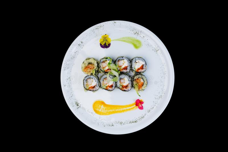 油煎的寿司用黄瓜、一些乳脂干酪、tobiko鱼子酱和虾 顶视图 查出在黑色背景 库存图片