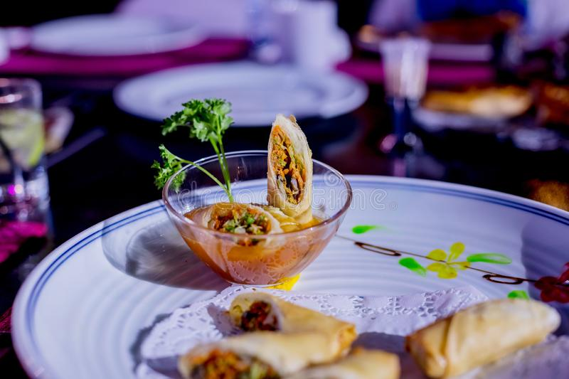 油煎的春卷用红色和白汁,供食在白色板材用在灰色背景的新鲜的蔬菜沙拉 亚洲 库存图片