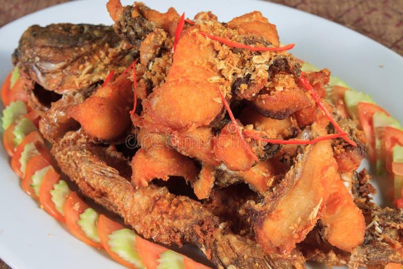 油煎的河鱼用大蒜和胡椒 免版税图库摄影