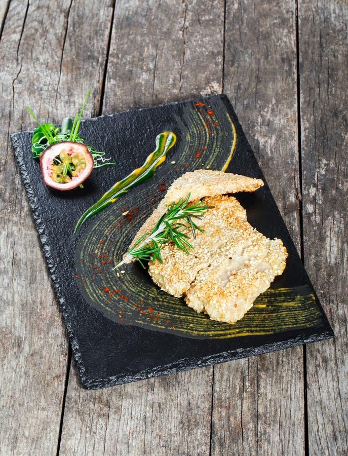 油煎的海鱼内圆角用迷迭香和芝麻在石板岩背景关闭 免版税库存图片