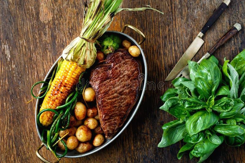 油煎的牛排菜煎锅木台式视图 库存图片