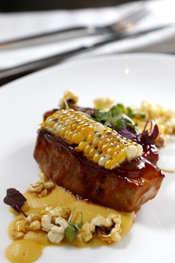 油煎的牛肉用在白色板材的烤玉米 图库摄影