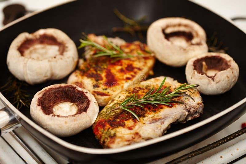 油煎的猪排和蘑菇蘑菇在煎锅 库存照片