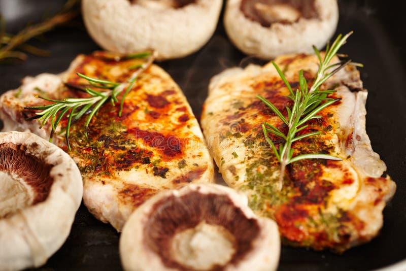 油煎的猪排和蘑菇蘑菇在煎锅 免版税库存图片