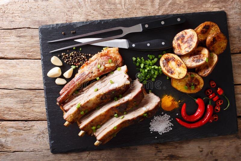 油煎的猪排用大蒜和辣椒和被烘烤的土豆 图库摄影