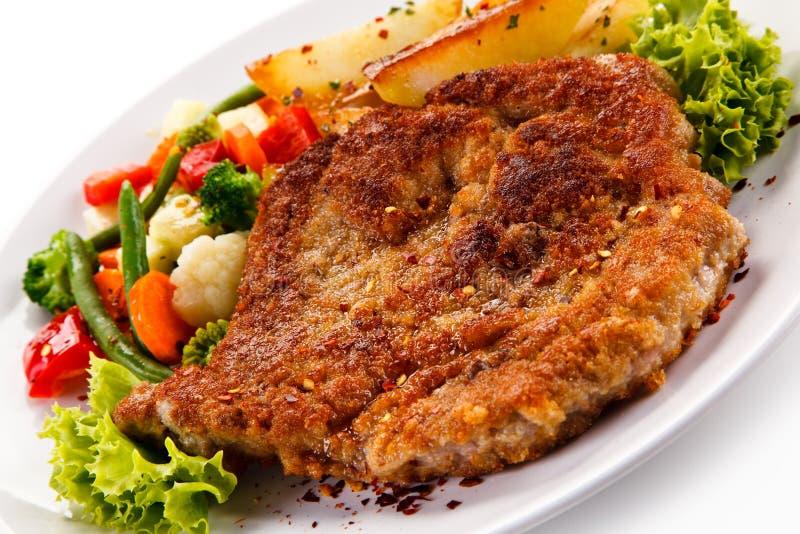 油煎的猪排用被烘烤的土豆和菜 免版税库存图片