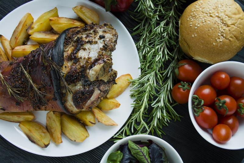 油煎的猪肉指关节用土豆在一块白色板材服务 装饰了用新鲜的保加利亚胡椒,迷迭香 r 免版税库存照片
