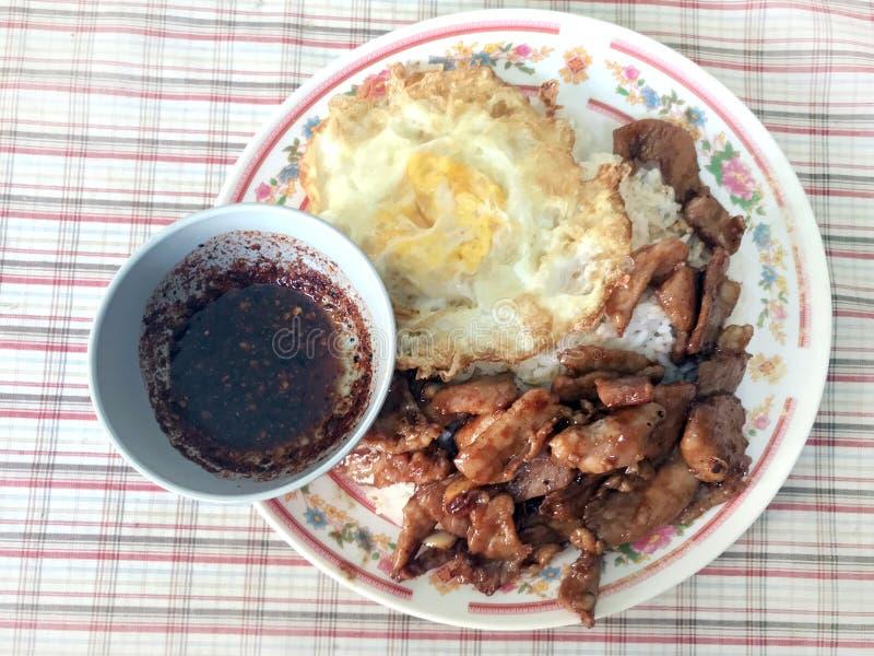 油煎的猪肉用在米荷包蛋的大蒜胡椒和辣椒蘸选择聚焦泰国菜单安逸的街道食物的辣调味汁 免版税图库摄影