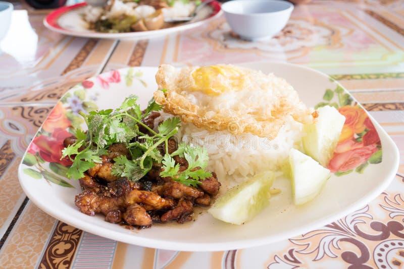 油煎的猪肉用大蒜和煎蛋在煮熟的米 图库摄影
