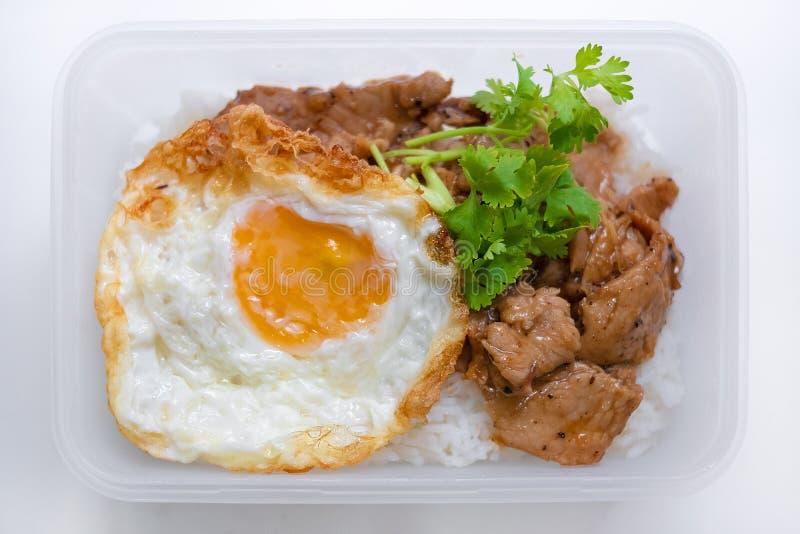 油煎的猪肉用大蒜胡椒和煎蛋在米在箱子isola 免版税图库摄影