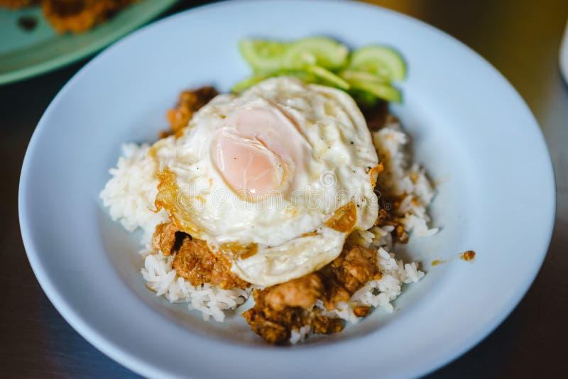 油煎的猪肉用大蒜胡椒和煎蛋在米 库存图片