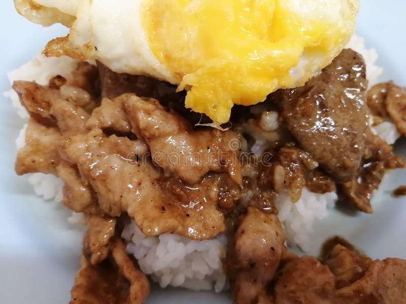 油煎的猪肉用大蒜,在米的荷包蛋 库存照片