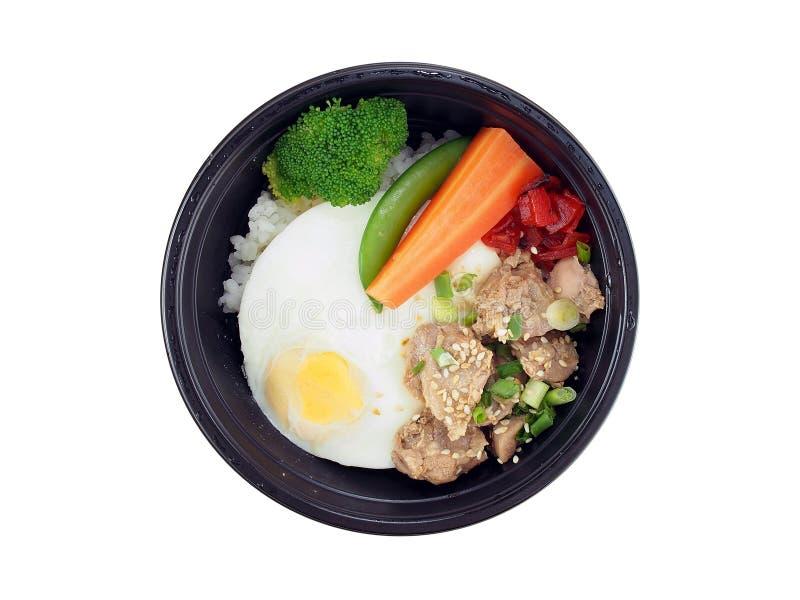 油煎的猪肉用韩国调味汁和米,与被蒸的菜的煎蛋在白色背景隔绝的黑塑料盘子 库存图片