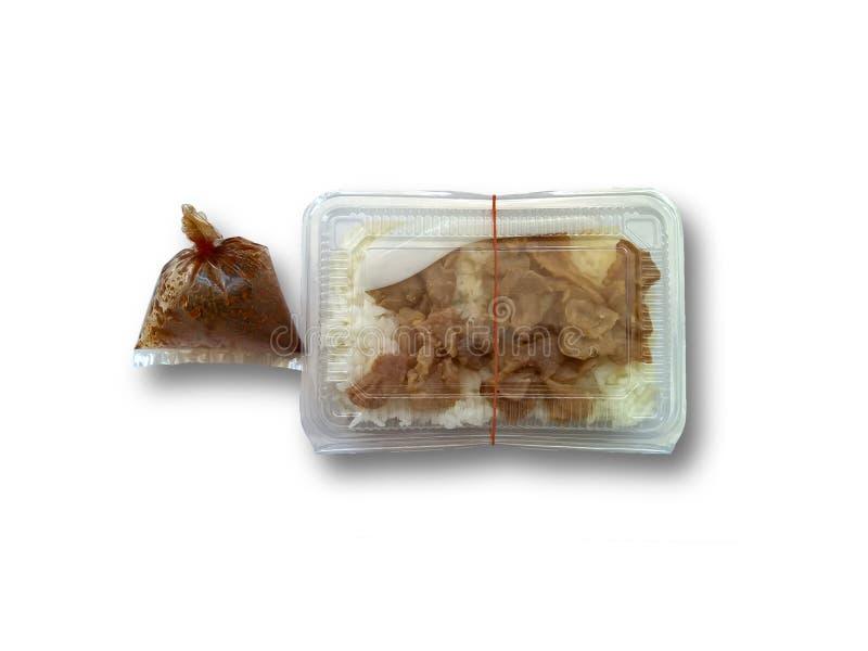 油煎的猪肉米和调味汁在清楚的塑料盒包裹在白色背景 图库摄影