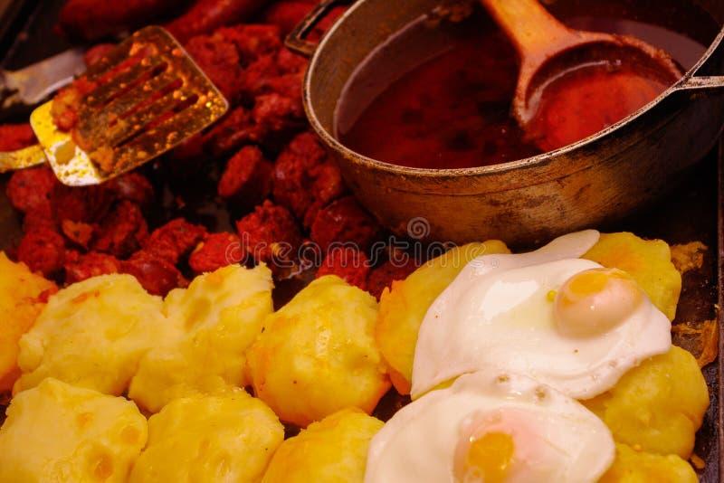 油煎的红色加调料的口利左香肠用potatoe玉米粉薄烙饼和煎蛋,传统厄瓜多尔盘 免版税库存图片