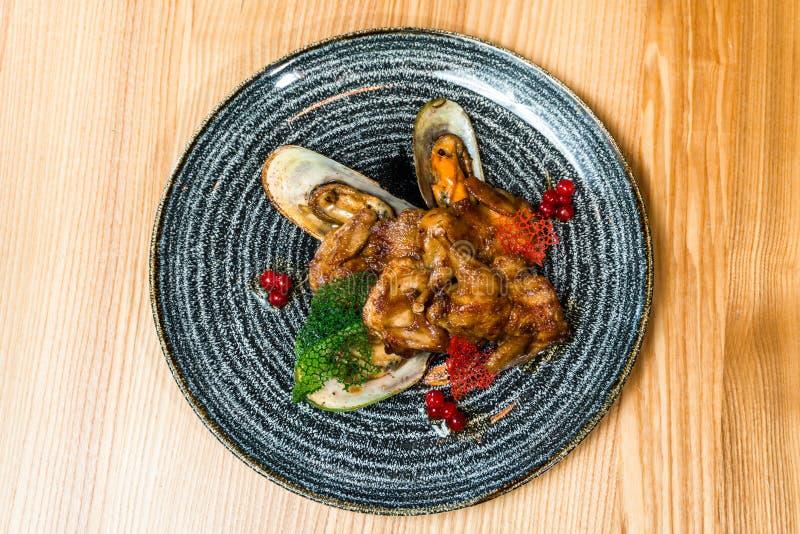 油煎的翼用在一个黑色的盘子的淡菜 免版税图库摄影