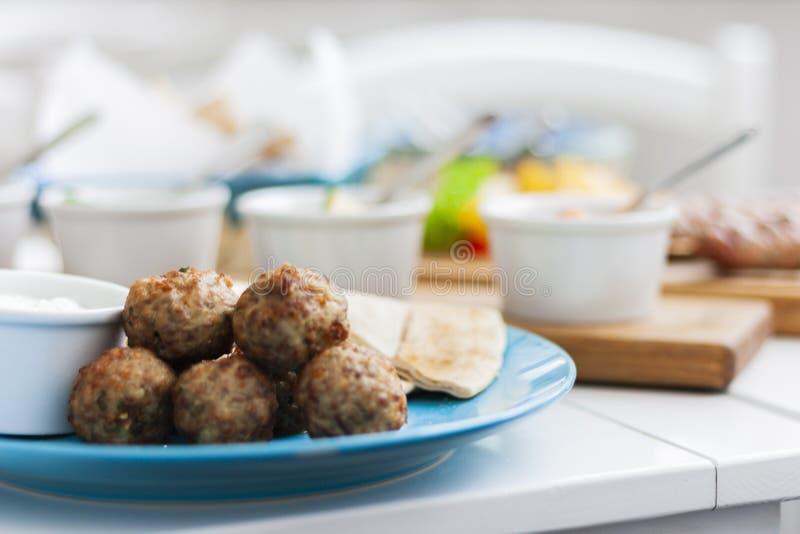油煎的肉丸用薄菏和苹果用白汁和平的蛋糕-传统希腊午餐在一块蓝色板材在餐馆 库存照片