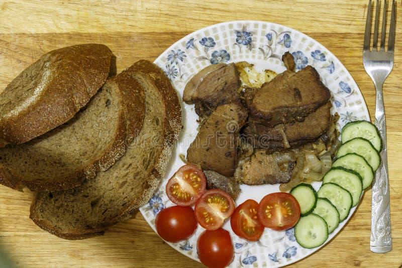 油煎的肉块菜和面包 库存图片