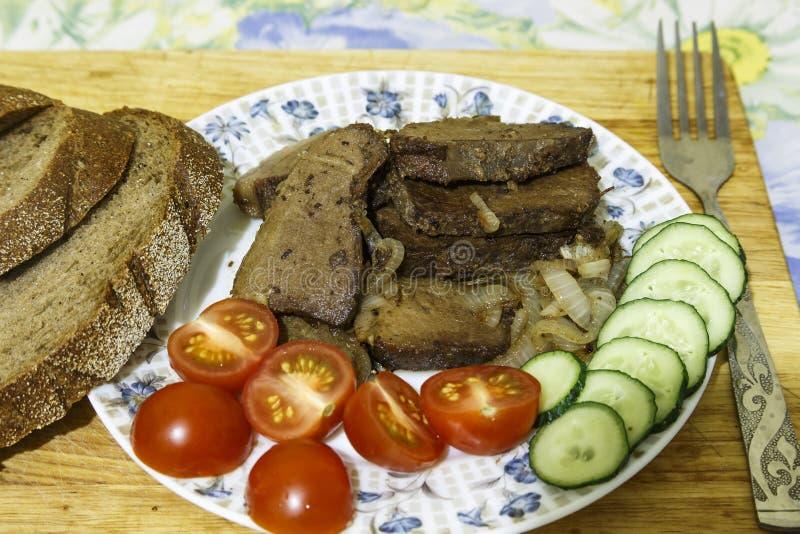 油煎的肉块菜和面包 库存照片