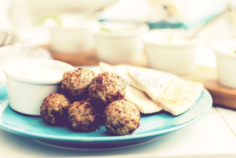 油煎的肉末用调味汁和玉米粉薄烙饼,在一块蓝色板材的传统希腊午餐在餐馆 免版税库存照片