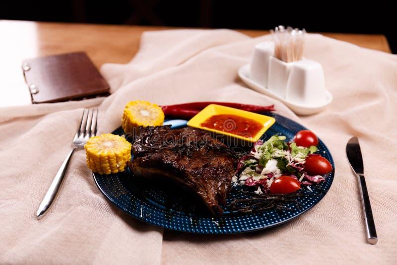 油煎的肉用煮沸的玉米在桌上供食 库存照片