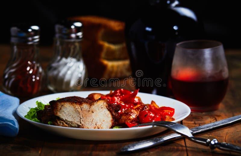 油煎的肉用水果和蔬菜装饰并且喝酒 免版税库存照片