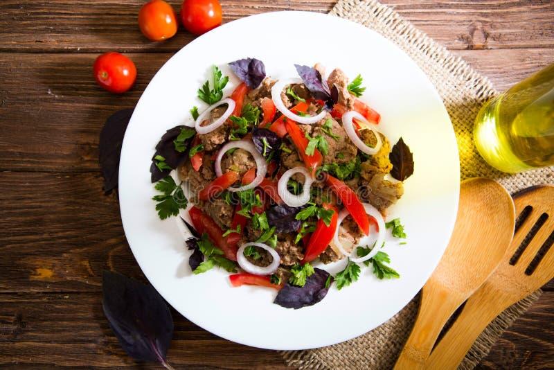 油煎的肝脏用葱和蕃茄在木背景 免版税图库摄影