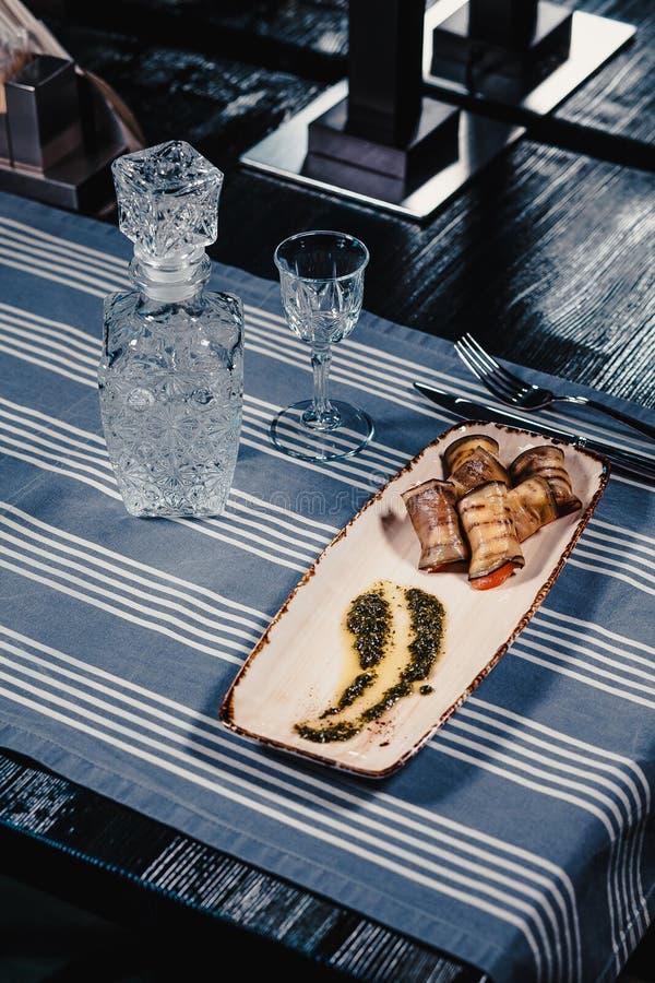 油煎的茄子充塞用蕃茄和乳酪在一块白色板材用调味汁 在一张蓝色桌布镶边与刀子和 库存图片