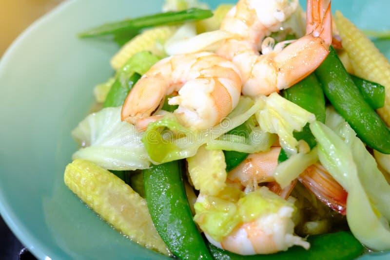 油煎的菜用虾或大虾在绿色板材 免版税库存照片