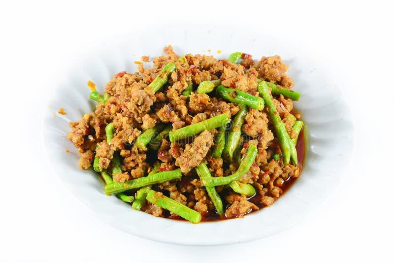 油煎的辣椒黏贴调味汁用猪肉用豇豆泰国食物,在白色的孤立 免版税库存照片