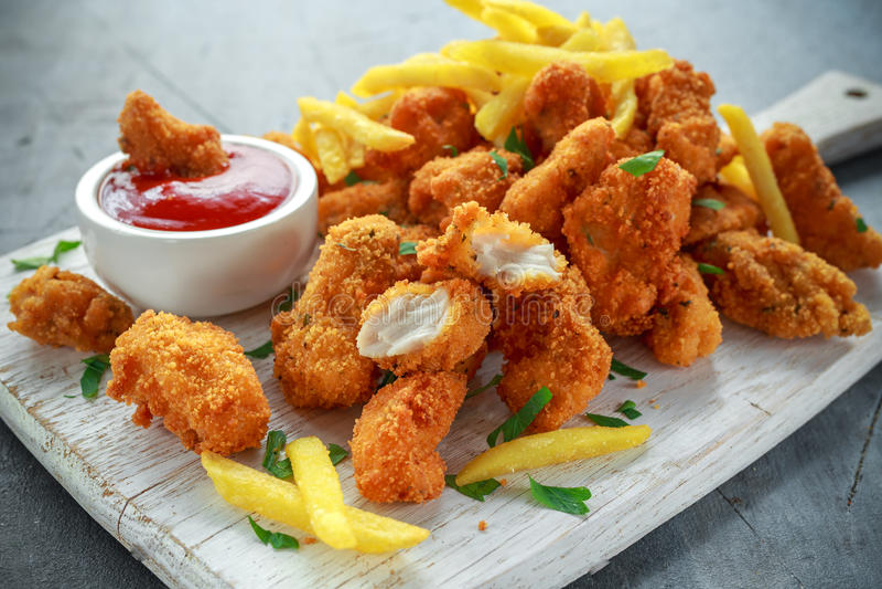 油煎的酥脆鸡块用炸薯条和番茄酱在白板 免版税库存照片