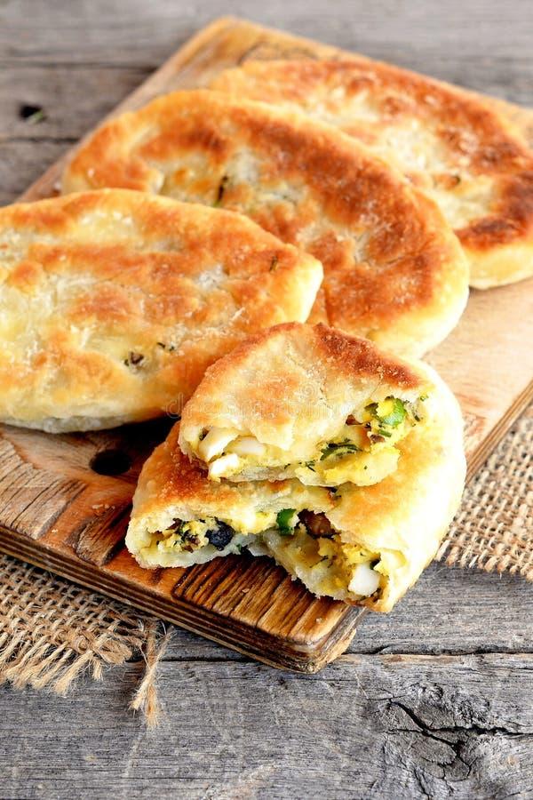 油煎的饼用蘑菇、鸡蛋、葱和莳萝在一个木板 免版税库存照片