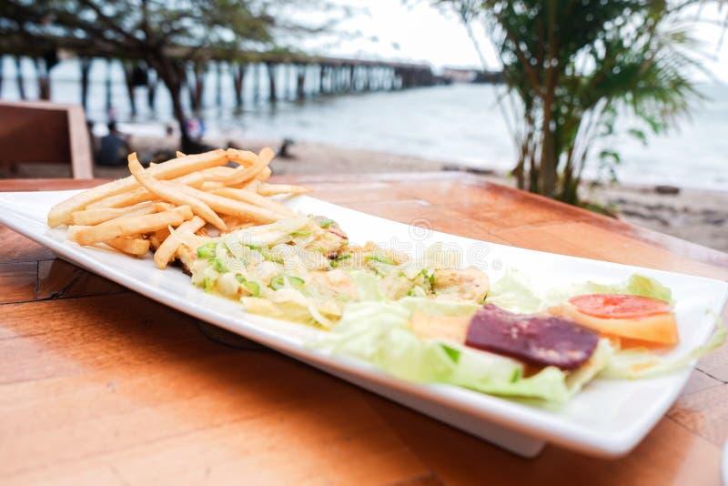 油煎的鱼片与菜和油煎的土豆在一个海滩在马那瓜尼加拉瓜 免版税库存照片