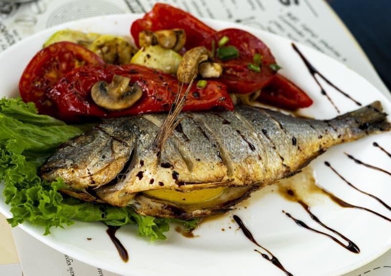 油煎的鱼用烤蕃茄和柠檬 棋 免版税库存图片