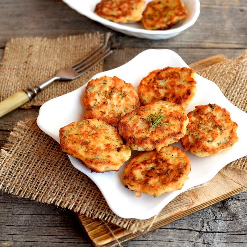 油煎的鱼糕在板材和在老木背景 从三文鱼肉烹调的炸肉排 可口和滋补午餐 免版税库存图片