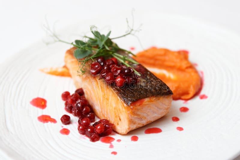 油煎的鲑鱼排用南瓜纯汁浓汤、莓果调味汁和草本 库存照片