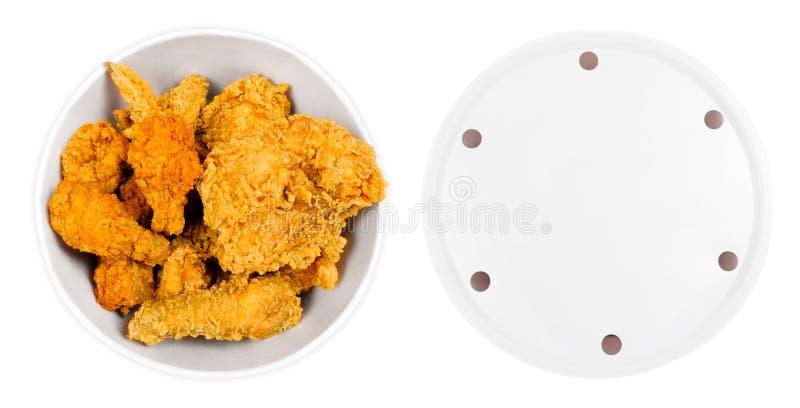 油煎的鸡翅和腿在白色桶箱子隔绝了 金黄布朗食物 面包的顶视图桶充分热和酥脆辣 免版税库存图片